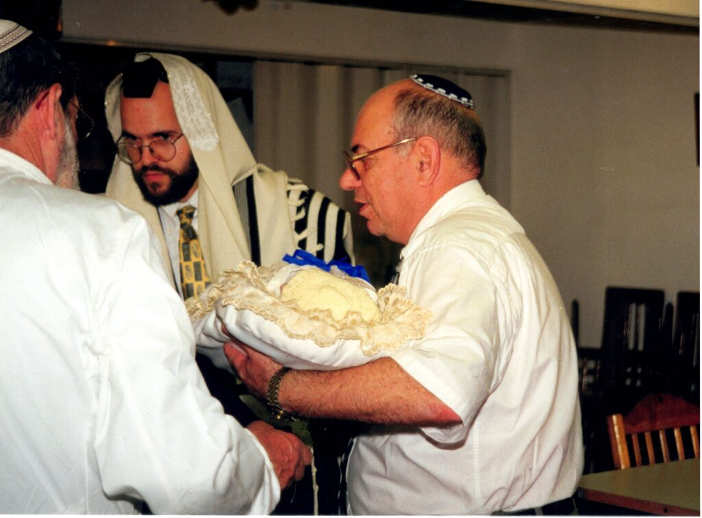 Father-in-Law handing Yitzchak Meir back to the Mohel