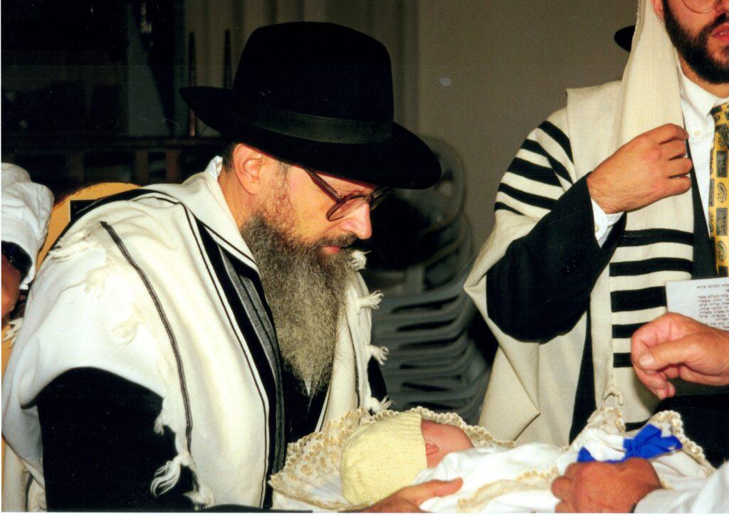 Rabbi Yitzchak Tratner, Sandek, holding Yitchak Meir